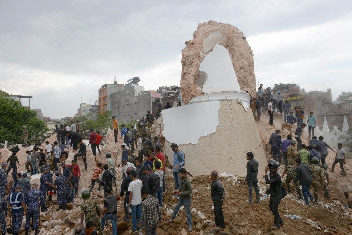 Nepalese rescue members gather at the collapsed Darahara Tower in Kathmandu on April 25, 2015.  A powerful 7.9 magnitude earthquake struck Nepal, causing massive damage in the capital Kathmandu with strong tremors felt across neighbouring countries.